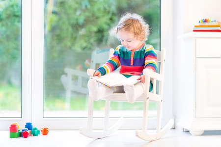 big window: Adorable toddler girl with curly hair wearing a colorful knitted dress reading a book and relaxing in a white rocking chair at home next to a big window