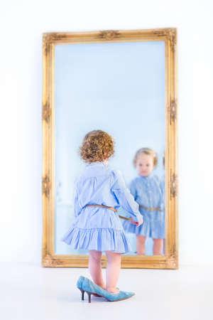 niñas pequeñas: La muchacha del niño pequeño con el pelo rizado hermoso con un vestido azul de pie delante de un gran espejo probándose zapatos de tacones altos de su madre s Foto de archivo