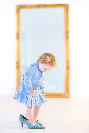 Funny toddler girl with beautiful curly hair wearing a blue dress is trying on her mother s high heels shoes in front of a big elegant mirror in a white bedroom  photo