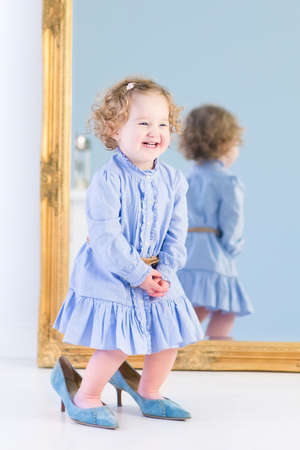 Beautiful toddler girl with curly hair wearing a blue dress standing in front of a big mirror trying on her mother s high heels shoes