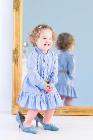 infant: Muchacha hermosa del ni�o con el pelo rizado con un vestido azul de pie delante de un gran espejo prob�ndose zapatos de tacones altos de su madre s