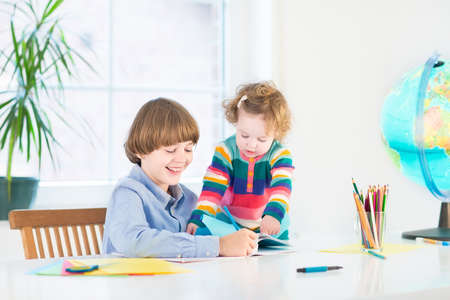 Happy children, young boy and his toddler sister, doing homework together at a white desk next to a window  photo