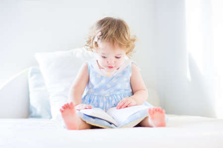 Funny toddler girl in a blue dress reading a book on a white bed in a sunny bedroom