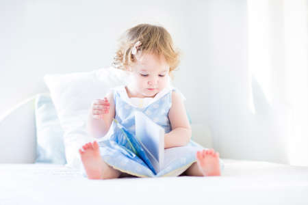 baby sit: Cute toddler girl with curly hair wearing a blue dress sitting on a white bed in a sunny bedroom reading a book  Stock Photo