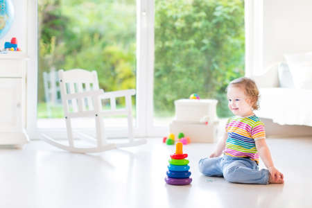 Adorable toddler girl playing with a colorful pyramid in a beautiful white room with a big window into the garden