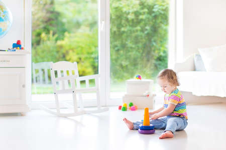 windows and doors: Cute toddler girl playing with a pyramid toy in a white room with a big window with garden view  Stock Photo
