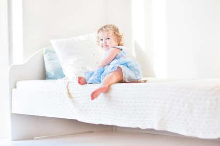 niño trepando: Muchacha linda del niño que se sienta en una cama blanca en casa en una mañana soleada