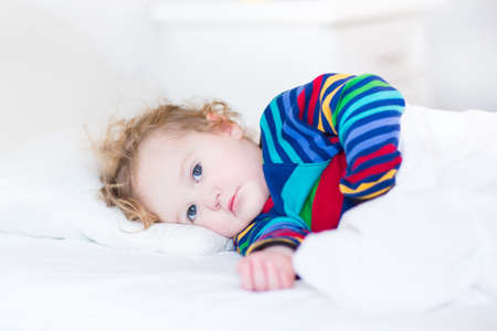 Cute toddler girl waking up in the morning in a sunny white bedroom  photo