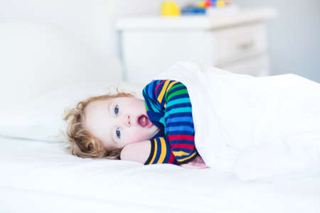 Funny yawning toddler girl waking up in the morning in a sunny white bedroom  photo