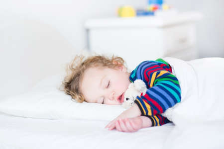 one little boy: Adorable toddler girl taking a nap in a white bed holding her teddy bear