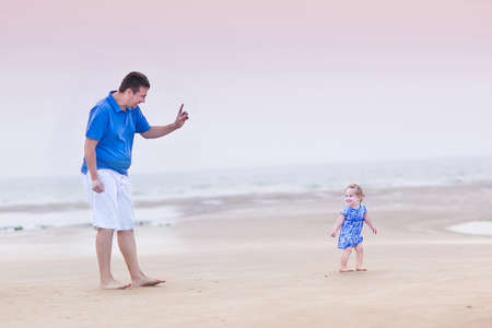 Happy young father playing with his cute toddler daughter on a beach at sunset  photo