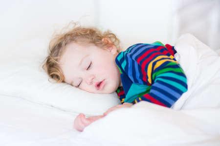Entzückendes Kleinkindmädchen, die ein Nickerchen in einem weißen sonnigen Schlafzimmer