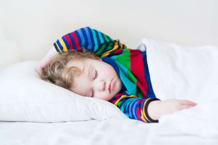 Funny sleeping toddler girl in a white bed  photo