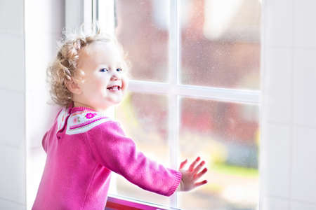 Beautiful little girl watching out of a window with autumn trees  photo