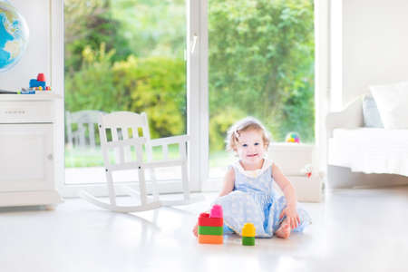 Beautiful toddler girl with curly hair wearing a blue dress playing in a white sunny bedroom with a big window with garden view