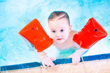 Cute toddler having fun in a swimming pool wearing red armbands for safety in water  photo
