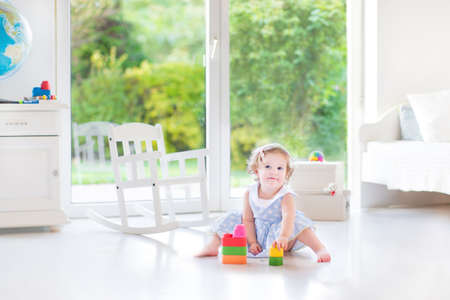 Funny toddler girl with curly hair wearing a blue dress playing in a white sunny bedroom with a big window with garden view  photo
