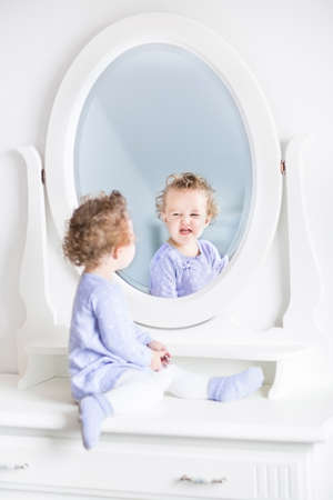looking: Adorable curly toddler girl making funny faces watching her reflection in a beautiful white mirror