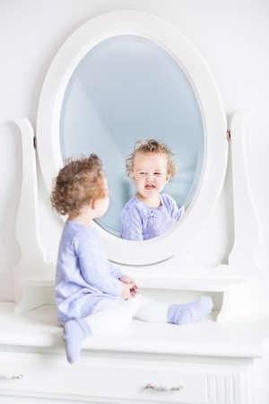 Schattig krullend peuter meisje het maken van grappige gezichten kijken naar haar spiegelbeeld in een mooie witte spiegel