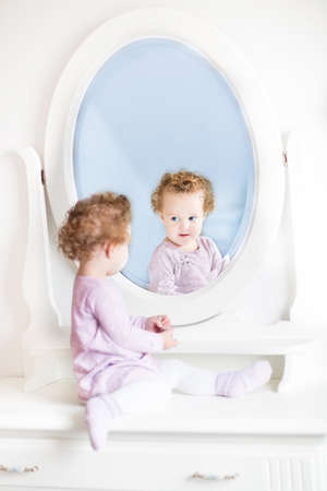 looking in mirror: Cute little toddler girl with curly hair looking at her reflection in a beautiful white mirror  Stock Photo