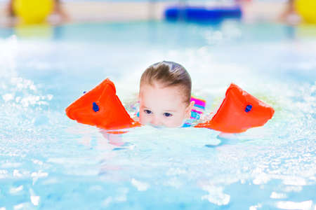 Cute toddler girl swimming in a pool with her face under water  photo
