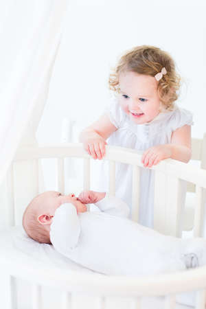 brothers and sisters: Adorable curly toddler girl in a white dress talking to her newborn baby brother in a white sunny bedroom with a round crib with canopy