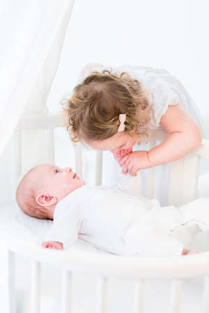 Cute toddler girl in a white dress kissing the hand of her baby brother relaxing in a white round crib