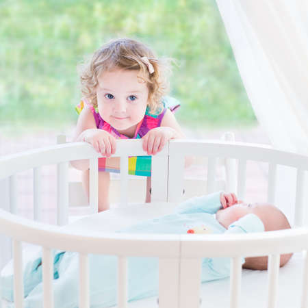 Cute toddler girl playing with her newborn baby brother in a white round bed next to a big window with garden view  photo