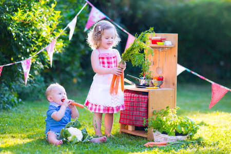 Funny curly little girl and adorable baby boy, cute brother and sister, playing together with a vintage wooden toy kitchen, table ware and fresh healthy vegetables in a sunny summer garden photo