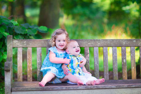 Adorable kids, little curly girl and a cute baby boy, brother and sister, sitting together on a wooden bench in a garden, hugging and kissing, relaxing and having fun on a sunny summer day photo