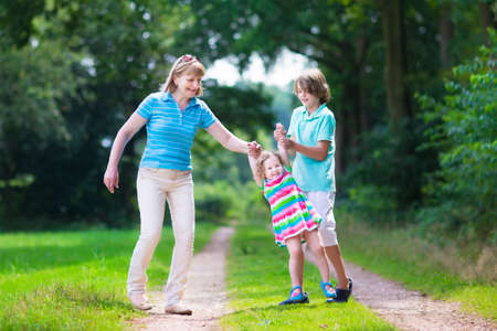 grand kid: Happy active woman enjoying hiking with two children, school age boy and cute curly toddler girl walking together in a beautiful pine wood forest on a sunny summer day