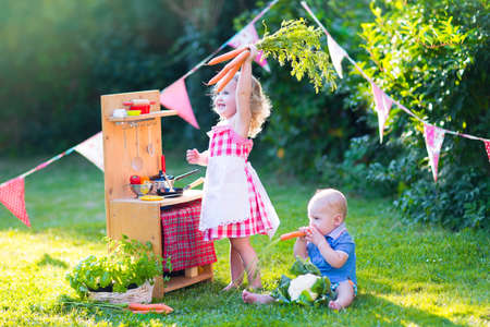ni�os cocinando: Ni�a divertida rizado y el beb� adorable, lindo hermano y hermana, jugando junto a una cocina de madera de la vendimia de juguetes, art�culos de mesa y verduras frescas y saludables en un jard�n soleado de verano Foto de archivo