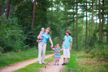 grand kid: Happy active woman enjoying hiking with three children, school age boy, cute toddler girl and a little baby, walking together in a beautiful pine wood forest on a sunny summer day
