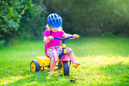 tricycle: Cute funny toddler girl riding her bike wearing a safety helmet enjoying a nice sunny day in a summer garden playing outdoors