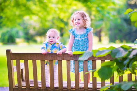 sitting on a bench: Adorable kids, little curly girl and a cute baby boy, brother and sister, sitting together on a wooden bench in a garden, hugging and kissing, relaxing and having fun on a sunny summer day Stock Photo