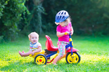 tricycle: Two happy kids, adorable curly toddler girl and a funny cute baby boy, brother and sister, playing together riding a bike, first colorful tricycle, having fun in the garden on a sunny summer day