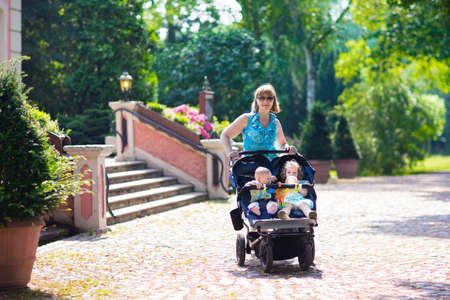 baby carriage: Woman with a double stroller