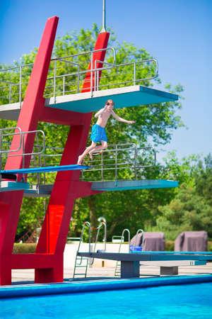 springboard: Activo adolescente muchacho valiente que salta en una piscina al aire libre de una alta torre con el aprendizaje trampolín para bucear durante la clase de deporte en un día caluroso de verano Foto de archivo