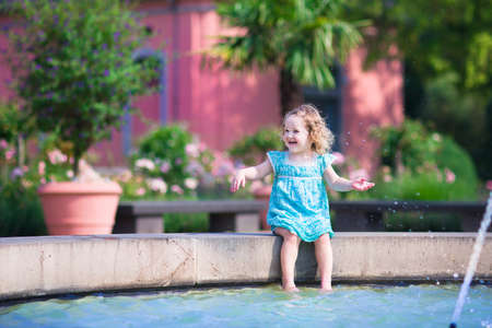 wet dress: Happy laughing little girl, adorable curly toddler in a blue dress, playing with water splashes refreshing in a fountain on a hot sunny summer day in a beautiful European city center