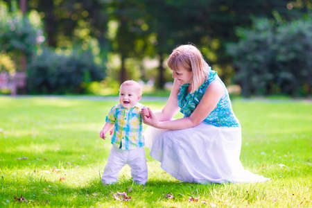 Beautiful young woman and a happy baby, cute little boy, playing together in a park, the child is learning to walk making his first steps in a sunny summer garden