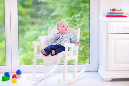 early summer: Cute funny baby, adorable little boy wearing a colorful shirt relaxing in a white rocking chair next to a big garden view window at home or daycare center