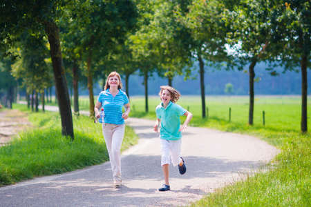 Happy healthy family, active young woman and a funny laughing boy, running together in a beautiful field, enjoying jogging sport outdoors on a sunny summer day photo