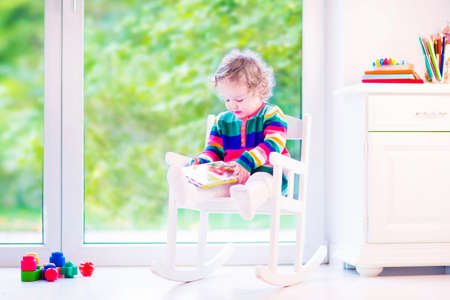 warm home: Cute curly little girl, funny toddler wearing a warm colorful knitted dress reading a book relaxing in a white rocking chair next to a big garden view window at home or daycare center