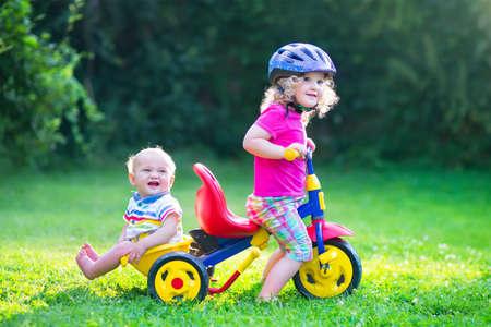 andando en bicicleta: Dos niños felices, adorable niña rizado niño y un chico lindo bebé divertido, hermano y hermana, jugando juntos en bicicleta, primer triciclo colorido, la diversión en el jardín en un día soleado de verano