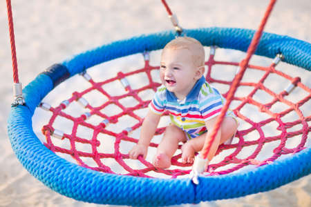 jungle gym: Happy laughing baby, adorable little boy enjoying a swing ride having fun on a playground in summer