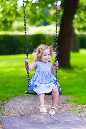 Happy laughing toddler girl with curly hair wearing a blue dress enjoying a swing ride on a sunny summer playground in a park Stock Photo