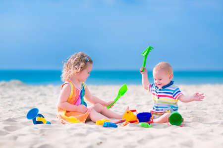 행복한 아기 소년과 작은 곱슬 유아 소녀, 형제와 자매, 청록색 물과 아름다운 이국적인 열대 해변에서 모래에 파고 장난감 양동이 플라스틱 삽으로 재