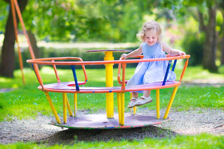 Happy laughing child, beautiful little toddler girl with culy hair wearing a blue dress having fun on a playground enjoying a swing ride on a hot summer day in a sunny city park Stock Photo