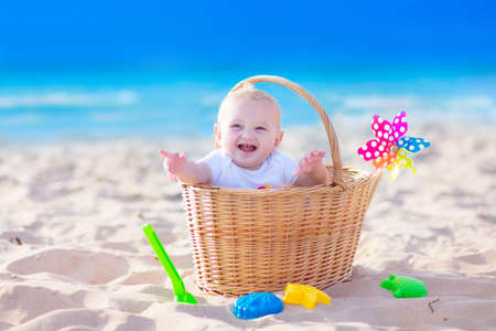 Happy funny baby, adorable blond laughing boy sitting in a basket playing with plastic beach toys, colorful bucket and shovel having fun during family picnic on tropical ocean coast