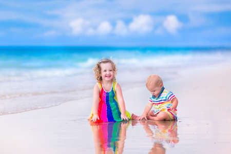 Happy baby boy and little curly toddler girl, brother and sister, playing with toy buckets and plastic shovel digging in sand on a beautiful exotic tropical beach with turquoise water  photo